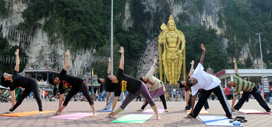 Yoga enthusiasts perform yogic asanas at the International Day of Yoga celebrations in front of Batu Caves in Malaysia